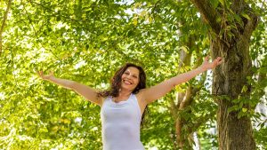 happy woman in menopause raises her arms to the sky in a garden, joyfully living the change of life
